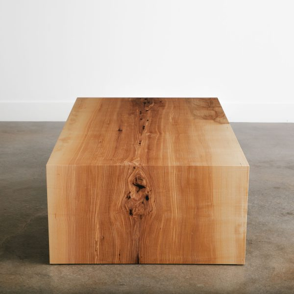 Folded base coffee table with natural tree character in light wood color