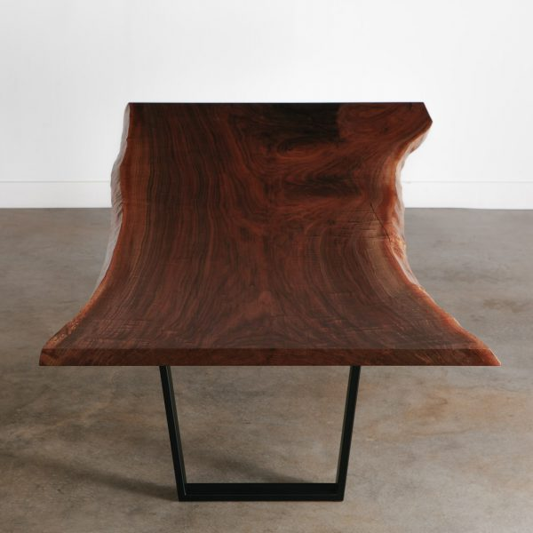 Large single slab rich walnut dining room table at Elko Hardwoods furniture store in Chicago