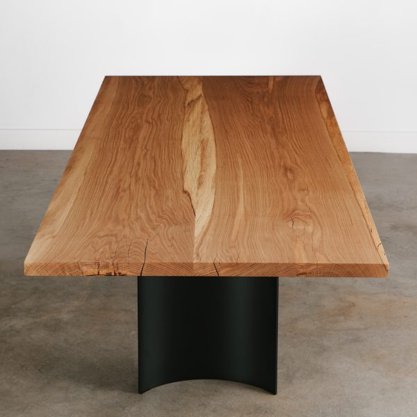 Bookmatched oak slab dining table with curved steel base